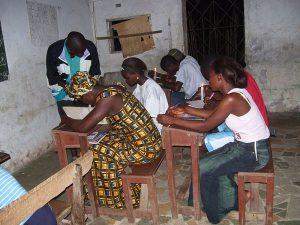 Estudiantes del Condado de Bong, Liberia, estudiando a la luz de una vela. Estos alumnos perdieron días de colegio durante la guerra civil de Liberia. Fotografía de dominio público proporcionada por la Agencia de los Estados Unidos para el Desarrollo Internacional (USAID por sus siglas en inglés).